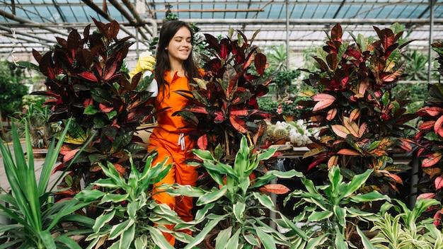 Vrouwelijk tuinman bespuitend water op installaties