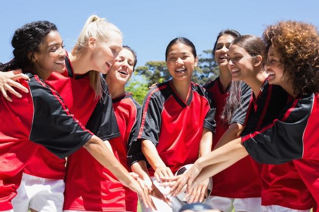 Vrouwelijk voetbalteam die handen stapelen