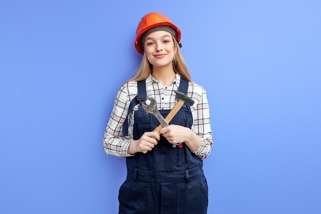 Vrouwelijke aannemer in oranje helm die zich met hulpmiddelen tegen blauwe muur bevindt