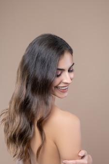 Vrouwelijke aantrekkelijkheid. blije glimlachende jonge vrouw die zich omdraait kijkend naar haar naakte schouder mooi en gelukkig