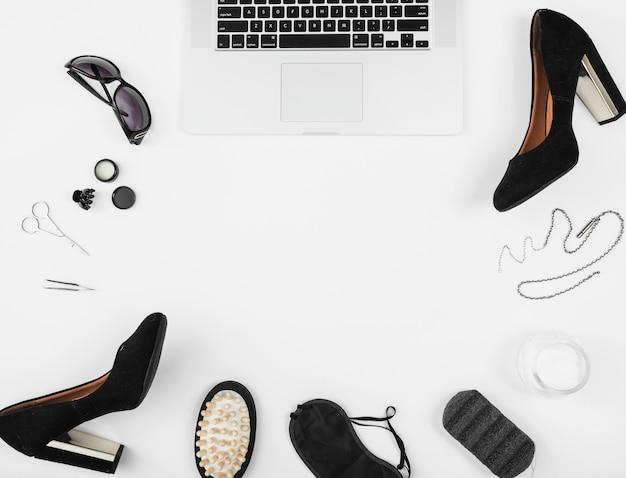 Vrouwelijke accessoires met open laptop op witte achtergrond