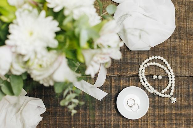 Vrouwelijke accessoires; trouwringen ; sjaal en bloemboeket op tafel