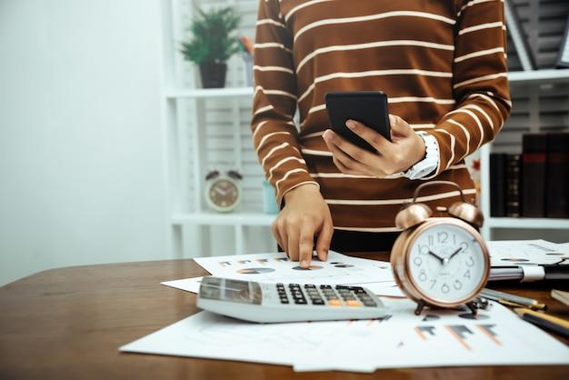 Vrouwelijke accountant die financiële gegevens bij bureau in modern bureau bekijken die over weekendvakantie dromen die van mening van venster genieten.