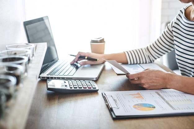 Vrouwelijke accountantberekeningen, audit en analyse van financiële grafiekgegevens met rekenmachine en laptop