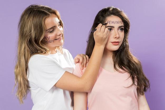 Vrouwelijke activisten schilderen hun gezichten