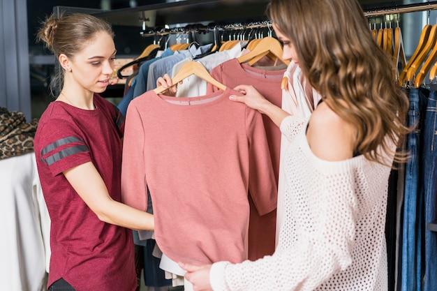 Vrouwelijke adviseur die vrouw helpen die bij kledingsopslag winkelen