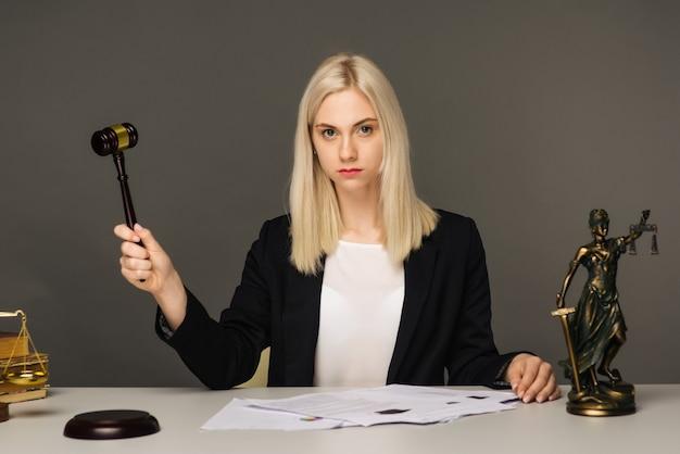 Vrouwelijke advocaat werkzaam aan tafel in kantoor