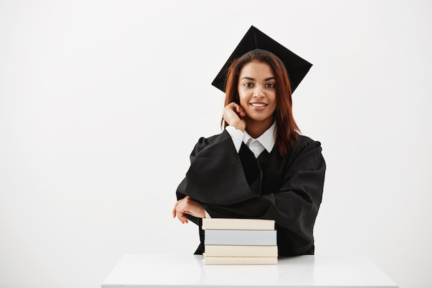 Vrouwelijke afgestudeerd in cap en mantel lachend zitten met boeken over witte oppervlak