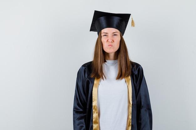 Vrouwelijke afgestudeerde camera kijken terwijl fronsen gezicht in uniforme, vrijetijdskleding en koppig op zoek. vooraanzicht.