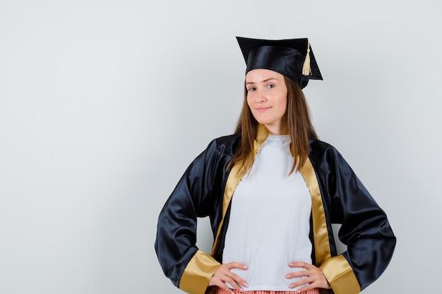 Vrouwelijke afgestudeerde die de handen op de taille in academische kleding houdt en er trots op kijkt. vooraanzicht.