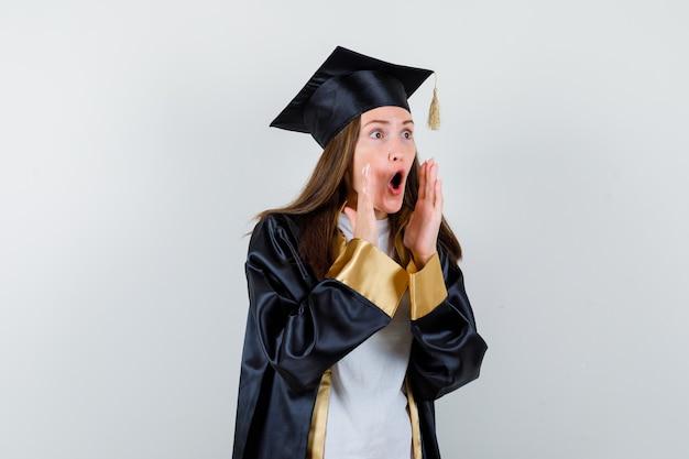 Vrouwelijke afgestudeerde die handen in de buurt van open mond in uniforme, vrijetijdskleding houdt en geschokt kijkt. vooraanzicht.