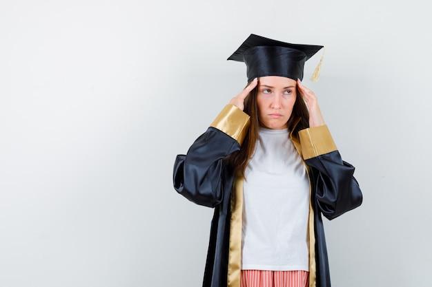 Vrouwelijke afgestudeerde die lijdt aan hoofdpijn in uniforme, vrijetijdskleding en op zoek moe, vooraanzicht.