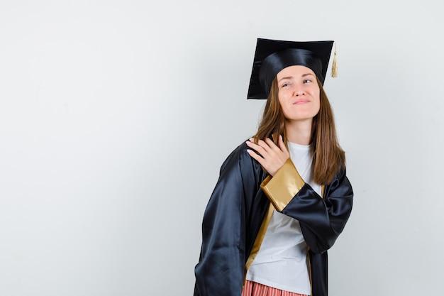 Vrouwelijke afgestudeerde die lijdt aan schouderpijn in uniforme, vrijetijdskleding en op zoek naar ongemakkelijk, vooraanzicht.