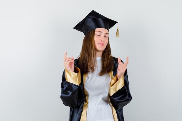 Vrouwelijke afgestudeerde die omhoog wijst in uniform, vrijetijdskleding en er vredig uitziet. vooraanzicht.