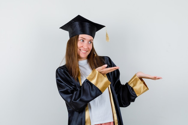 Vrouwelijke afgestudeerde die verwelkomend gebaar in uniform, vrijetijdskleding toont en vrolijk, vooraanzicht kijkt.