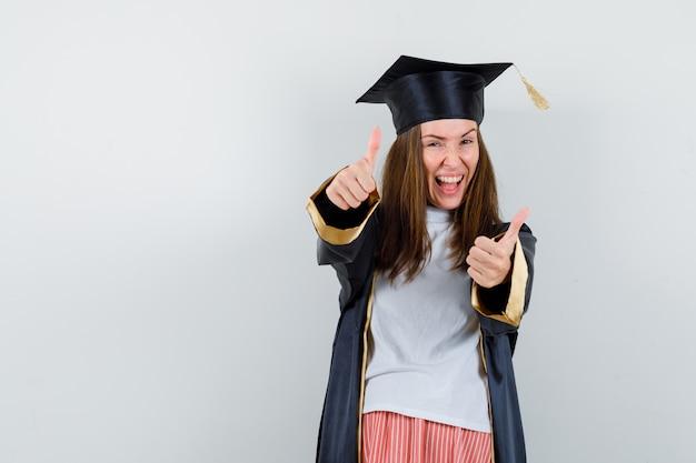 Vrouwelijke afgestudeerde dubbele duimen opdagen in uniforme, vrijetijdskleding en op zoek gelukkig. vooraanzicht.
