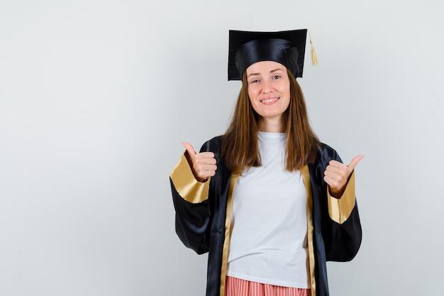 Vrouwelijke afgestudeerde dubbele duimen opdagen in uniforme, vrijetijdskleding en op zoek vrolijk. vooraanzicht.