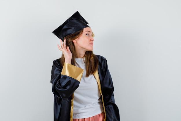 Vrouwelijke afgestudeerde hand achter oor houden in uniform, vrijetijdskleding en nieuwsgierig kijken. vooraanzicht.