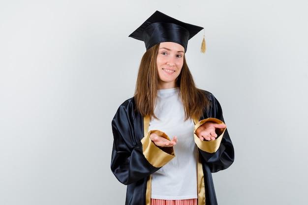 Vrouwelijke afgestudeerde handen spreiden op camera in uniforme, vrijetijdskleding en op zoek vrolijk, vooraanzicht.