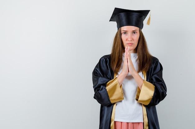 Vrouwelijke afgestudeerde houden handen biddend gebaar in uniforme, vrijetijdskleding en op zoek hoopvol. vooraanzicht.
