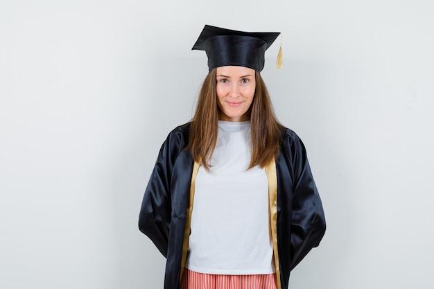 Vrouwelijke afgestudeerde houdt handen achter rug in uniform, vrijetijdskleding en kijkt beschaamd, vooraanzicht.