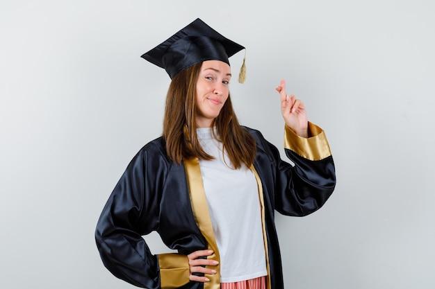 Vrouwelijke afgestudeerde houdt vingers gekruist in academische kleding en kijkt gelukkig, vooraanzicht.