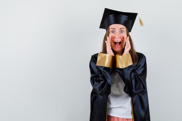 Vrouwelijke afgestudeerde in uniform, vrijetijdskleding die iets schreeuwt of aankondigt en opgewonden kijkt, vooraanzicht.