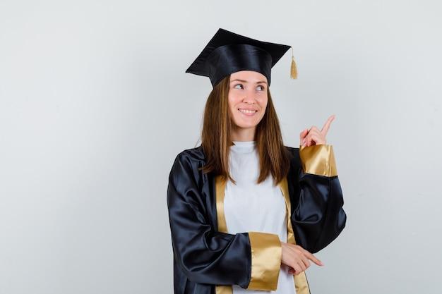 Vrouwelijke afgestudeerde in uniform, vrijetijdskleding die omhoog wijst en hoopvol, vooraanzicht kijkt.
