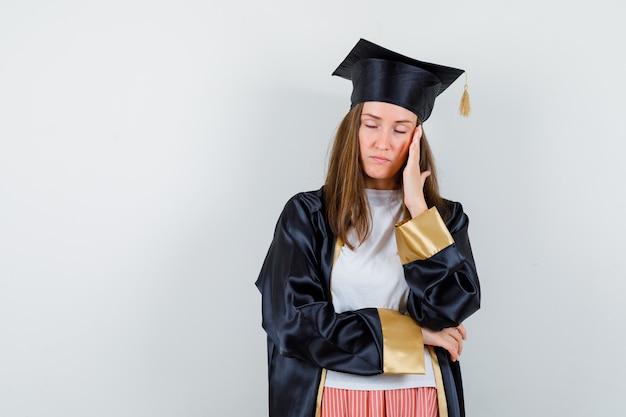 Vrouwelijke afgestudeerde in uniform, vrijetijdskleding met hoofdpijn en op zoek uitgeput, vooraanzicht.