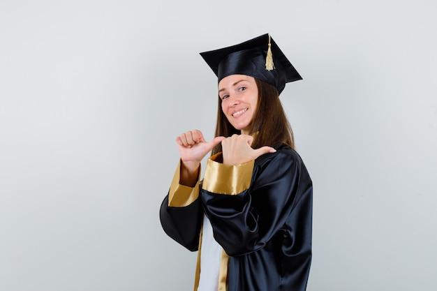 Vrouwelijke afgestudeerde in uniform, vrijetijdskleding wijst met duimen terug en kijkt hoopvol, vooraanzicht.