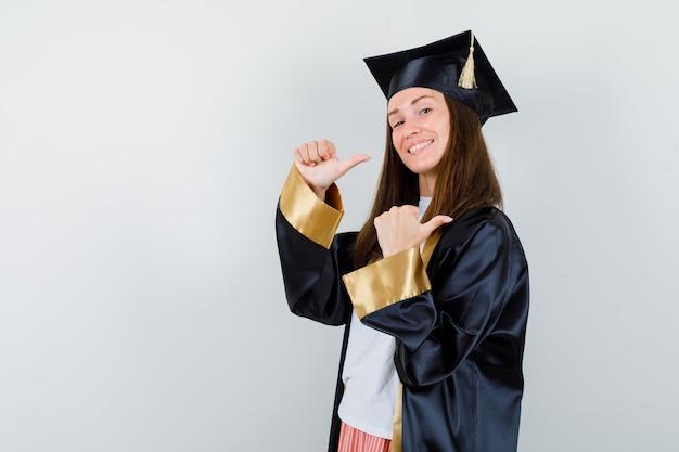 Vrouwelijke afgestudeerde in uniform, vrijetijdskleding wijst met duimen terug en kijkt vrolijk, vooraanzicht.
