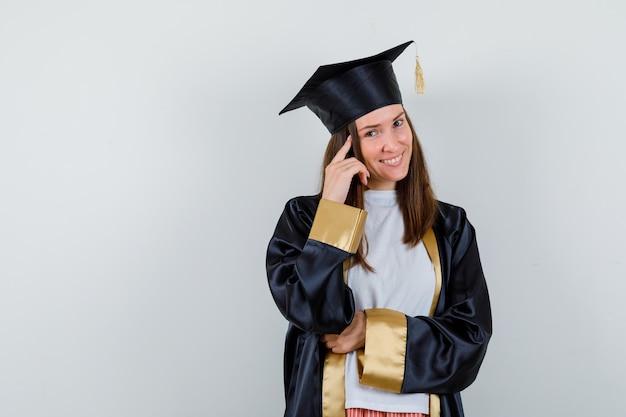 Vrouwelijke afgestudeerde in uniforme, vrijetijdskleding die de vinger op de tempels houdt en er vrolijk, vooraanzicht uitziet.