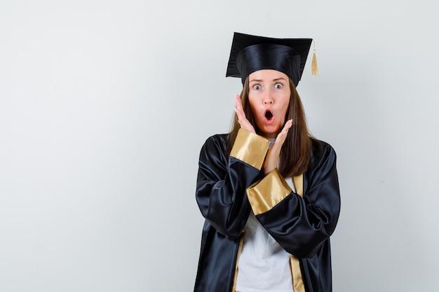 Vrouwelijke afgestudeerde in uniforme, vrijetijdskleding die handen in de buurt van gezicht houdt en geschokt, vooraanzicht kijkt.