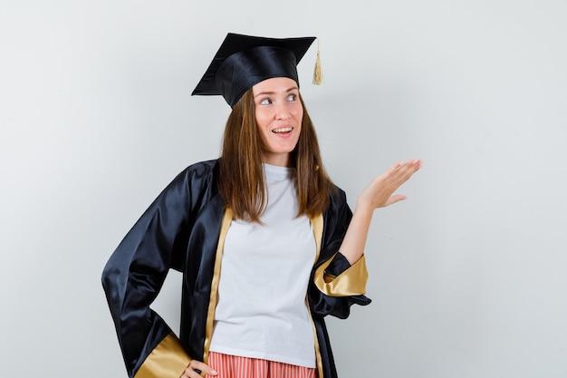 Vrouwelijke afgestudeerde in uniforme, vrijetijdskleding die iets toont terwijl hij omhoog kijkt en vrolijk, vooraanzicht kijkt.