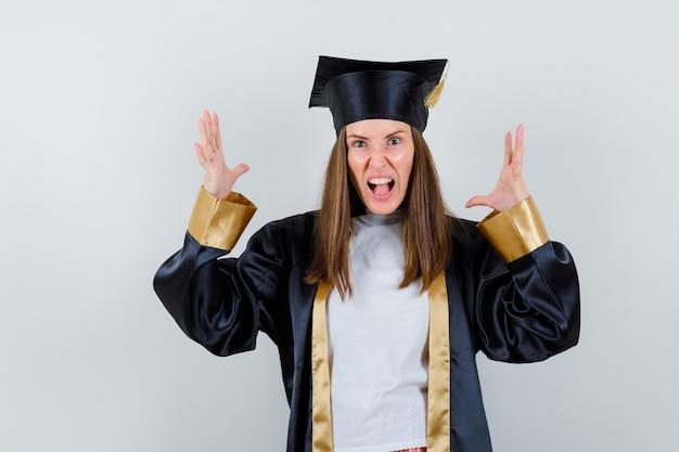 Vrouwelijke afgestudeerde in uniforme, vrijetijdskleding die op agressieve wijze handen opheft en geïrriteerd, vooraanzicht kijkt.