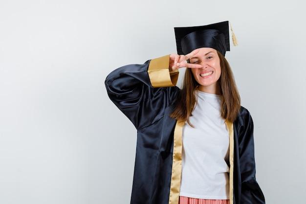 Vrouwelijke afgestudeerde in uniforme, vrijetijdskleding die overwinningsgebaar op oog toont en vrolijk, vooraanzicht kijkt.