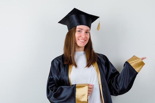 Vrouwelijke afgestudeerde in uniforme, vrijetijdskleding die verwelkomend gebaar toont en vrolijk, vooraanzicht kijkt.