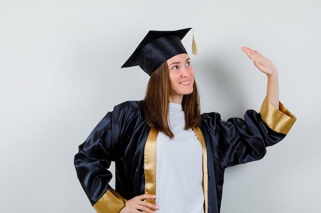 Vrouwelijke afgestudeerde in uniforme, vrijetijdskleding zwaait met de hand om afscheid te nemen en kijkt blij, vooraanzicht.