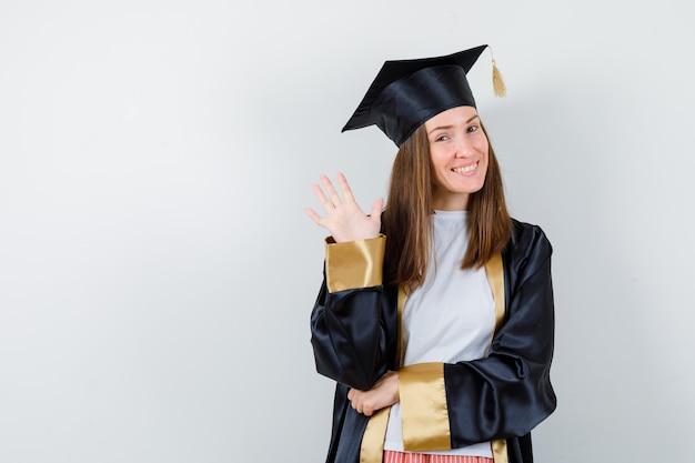 Vrouwelijke afgestudeerde in uniforme, vrijetijdskleding zwaait met de hand om afscheid te nemen en kijkt vrolijk, vooraanzicht.