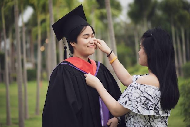 Vrouwelijke afgestudeerde knuffelen elkaar met haar vriend feliciteren met de universiteit.