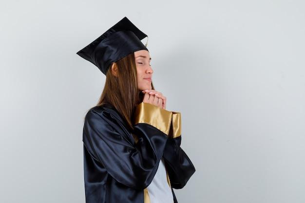 Vrouwelijke afgestudeerde omklemde handen in biddend gebaar in uniform en op zoek naar vredig, vooraanzicht.