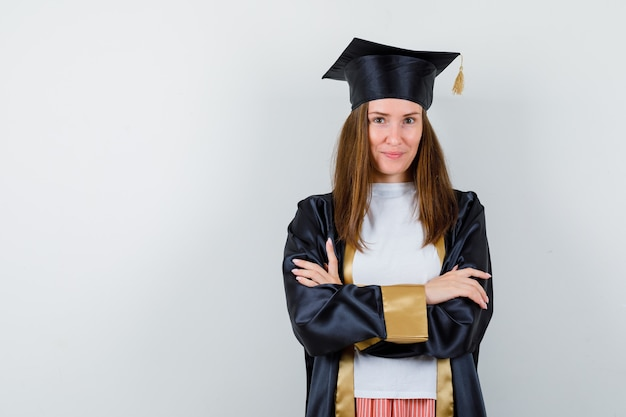 Vrouwelijke afgestudeerde permanent met gekruiste armen in uniforme, vrijetijdskleding en trots op zoek. vooraanzicht.