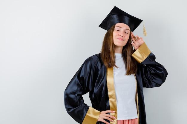 Vrouwelijke afgestudeerde poseren met vingers hoofd in uniforme, vrijetijdskleding aan te raken en op zoek ontspannen, vooraanzicht.