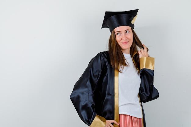 Vrouwelijke afgestudeerde poseren terwijl ze haar streng in uniforme, vrijetijdskleding vasthoudt en er dromerig uitziet, vooraanzicht.