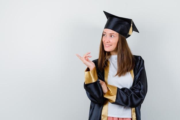 Vrouwelijke afgestudeerde wijst opzij in uniform, vrijetijdskleding en ziet er vrolijk uit. vooraanzicht.