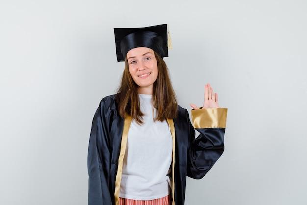 Vrouwelijke afgestudeerde zwaaiende hand voor begroeting in academische kleding en vrolijk op zoek. vooraanzicht.