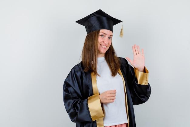Vrouwelijke afgestudeerde zwaaiende hand voor begroeting in uniforme, vrijetijdskleding en op zoek vrolijk, vooraanzicht.