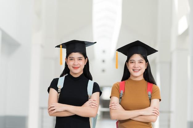 Vrouwelijke afgestudeerden met zwarte hoeden, gele kwastjes, glimlachend en gelukkig op de dag van afstuderen