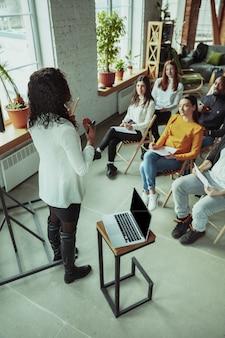 Vrouwelijke afrikaans-amerikaanse spreker die presentatie in zaal geeft op universitaire workshop