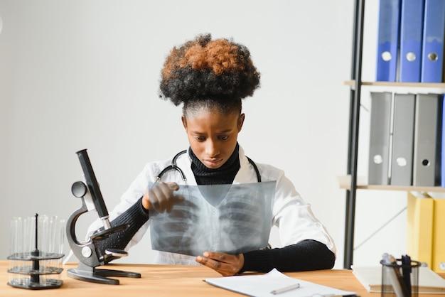 Vrouwelijke afrikaanse amerikaanse arts die witte jas met stethoscoop achter bureau in het bureau draagt en x-ray beeld kijkt